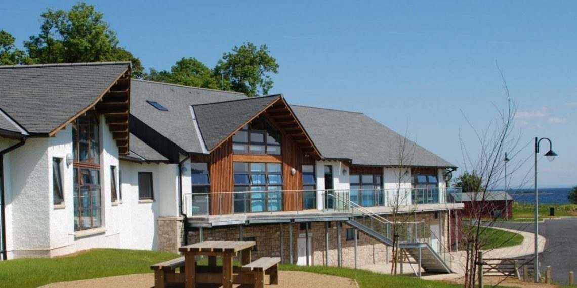 A view of the frontage of Arran Outdoor Education Centre, with windows out to the bay