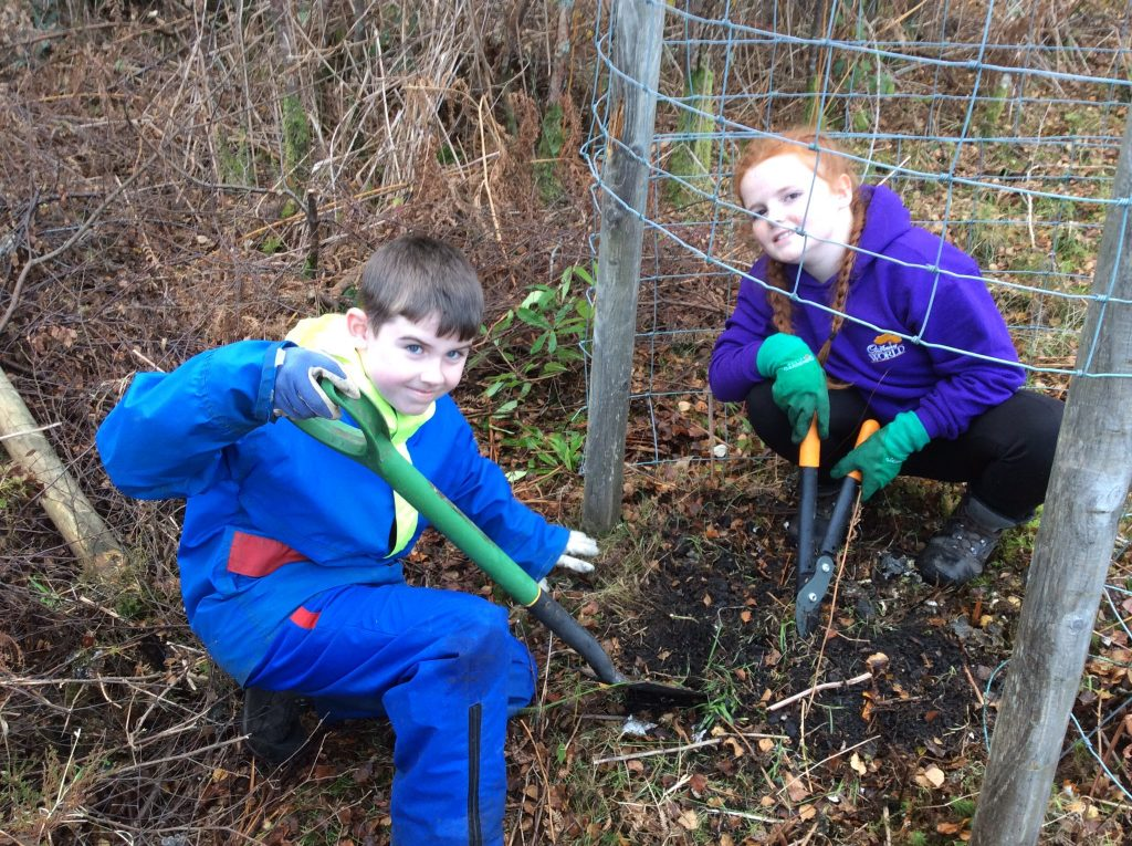 Two children digging soil on a conservation trip