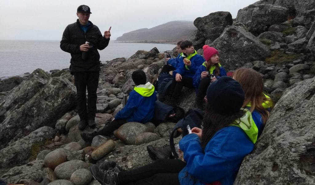 An instructor talking to a group of children on the rocky coastline